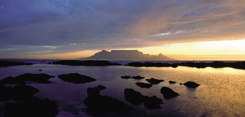 Table Mountain as sun set with yellow sky and silhouette of rocks in the sea.