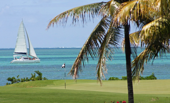 Golf green in Mauritius with passing catamaran boat.