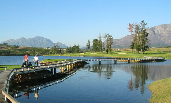 golfers walking across the bridge on the lake at De Zalze to play their shots.