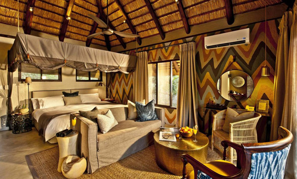 Colourful bedroom and lounge at safari lodge with thatched roof.