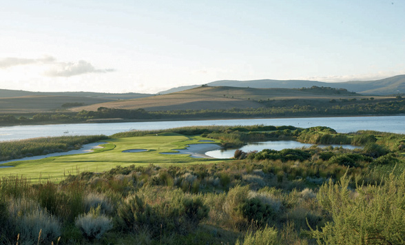 Lagoon surrounding the green and fairways of a golf course with hills beyond.