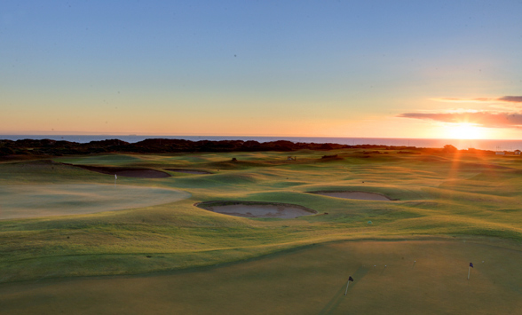 Sunsetting over the sea with long shadows on the golf course fairways.