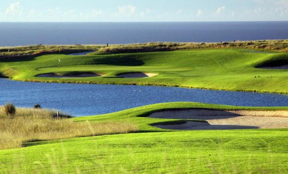 Green grass fairways on either side of the lake with bunkers surrounding the greens.