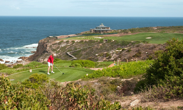 Lady in red top teeing off from 18th tee box across the fynbos towards the clubhouse with ocean in the distance.