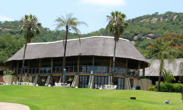 Thatched Clubhouse at Nelspruit Golf Course with palm trees in the foreground.
