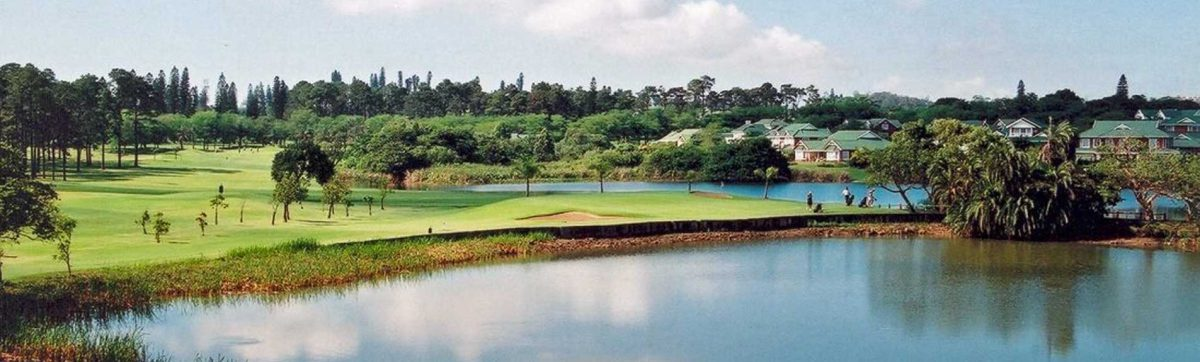 Golfers playing on the green fairways, surrounded by lakes and trees.