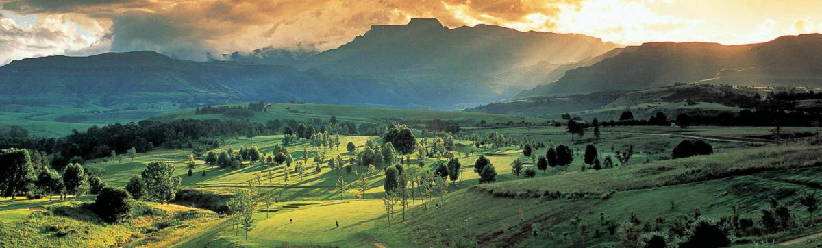 Evening sun casts long shadows across the fairways, silhouetting the mountains in the distance.