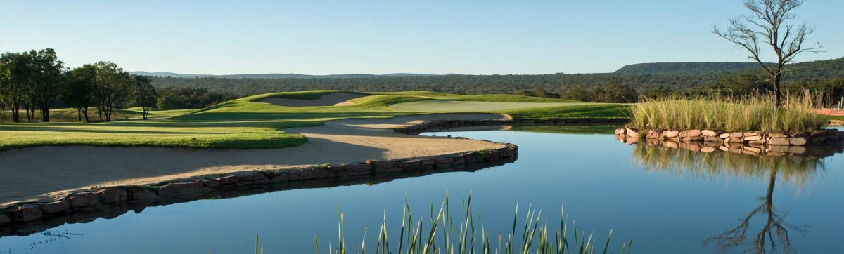 tranquil views across the lake at Legend Golf club with large sandy waste bunkers ready to catch errant golf balls that fall short of the green.