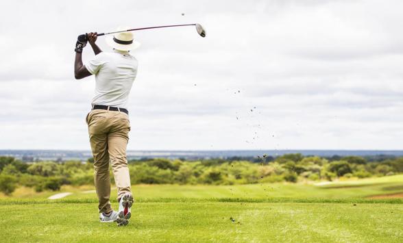 Golfer hitting ball off tee box at Euphoria Golf Club.