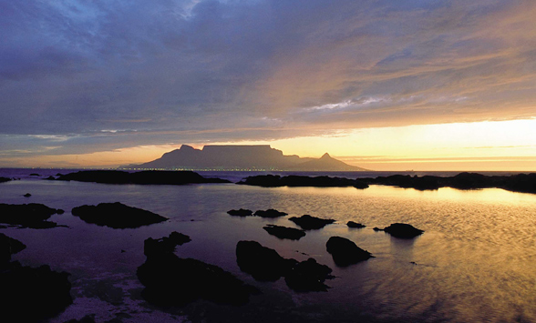 Sihouette of Table Mountain in the distance and rocks in the foreground with a yellow sky selected in the water.