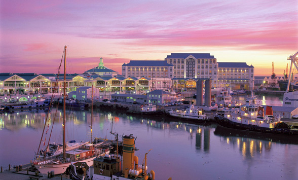 Pink sky reflected in the water of the harbour in Cape Town with lights and boats.