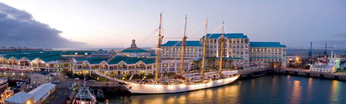 White hulled Tall Ship moored in the harbour at Cape Town with building and lights.