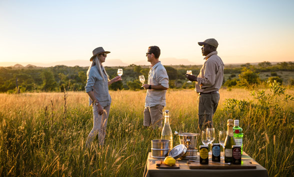 Couple enjoying sun downer drinks as part of their safari holiday.