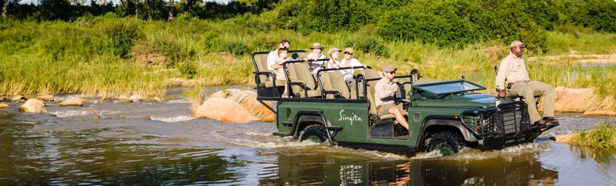 Family on a game drive vehicle as it ploughs through the Sand river.