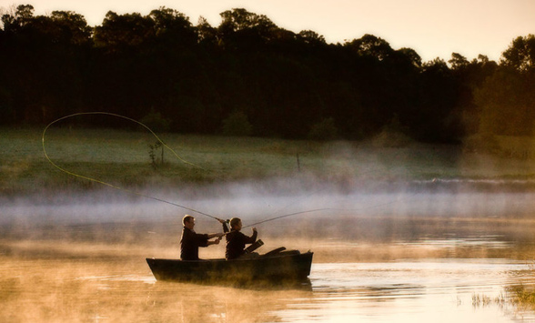 Fly fishing on the lake at Hartford House as the mist clears.