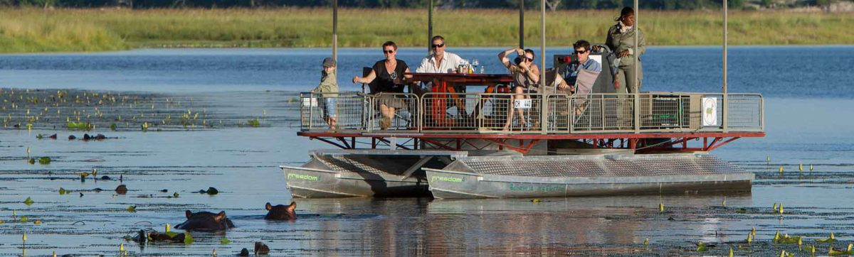 Tourist family watching hippos from a safari cruise on the Chobe river.