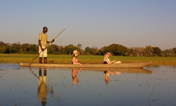 couple enjoy a canoe safari as the sun begins to set over the water.