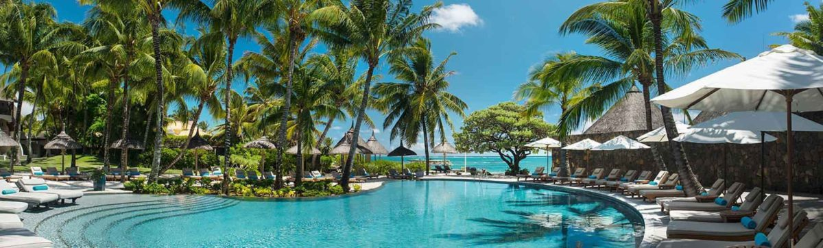Sun loungers and restaurants surround the pool close to the beach in Mauritius.
