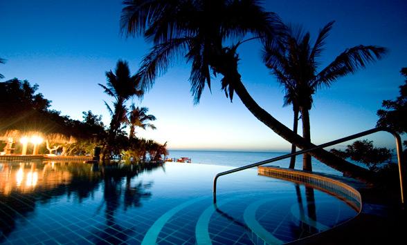sun setting in Bazaruto over the swim up pool bar at the Anantara Island Resort.