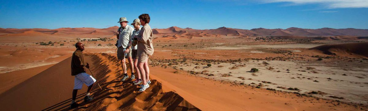Tourists on the top of he red dunes in Sossusveli, Namibia.