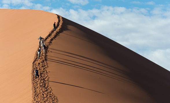 Tourists climbing the red dunes at Sossusvlei in Namibia.