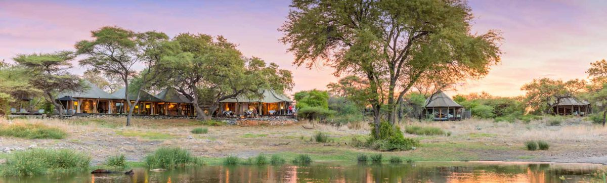 view across the waterhole to the Onguma tented camp at sunset.