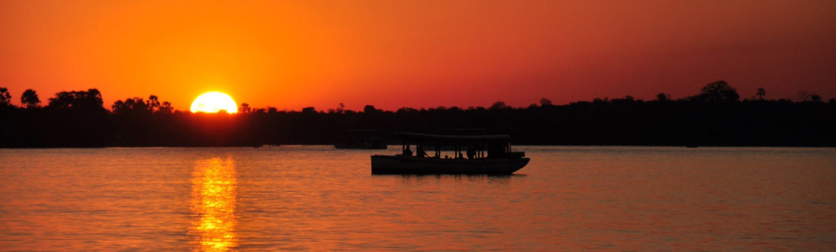 Orange African sun setting over the banks of the Zambezi River as guests enjoy sundowner drinks cruise.