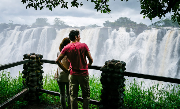 two people watching at the water flowing over the Victoria Falls in Zambia.