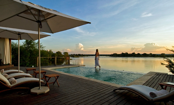 lady enjoying a sunset stroll by the pool at Sussi and Chuma as sun sets over the Zambezi River