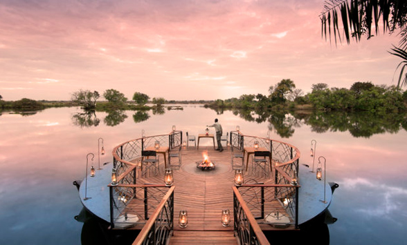 sun sets over the zambezi river as the fire pit is lit at Thorntree River Lodge.