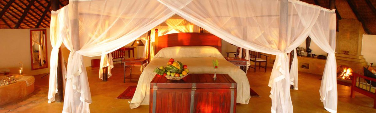 romantic honeymoon suite with king size bed draped in muslin mosquito nets and flowers.