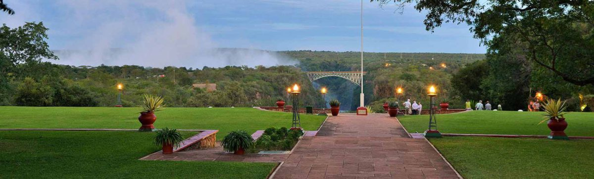 dusk sets over the lawn at the Victoria Falls Hotel with views of the spray from the falls hangs in the air.