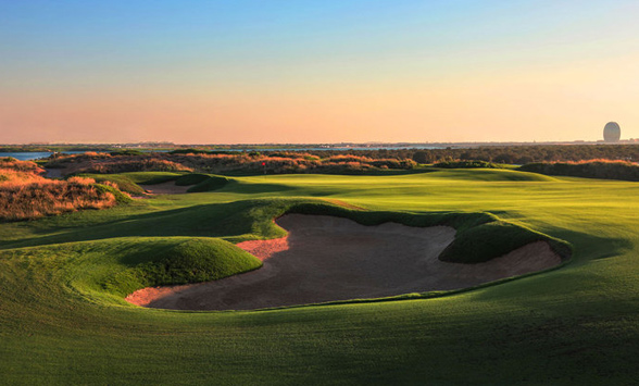 long shadows across the golf course fairways and the last rays of sun light up the bunkers.