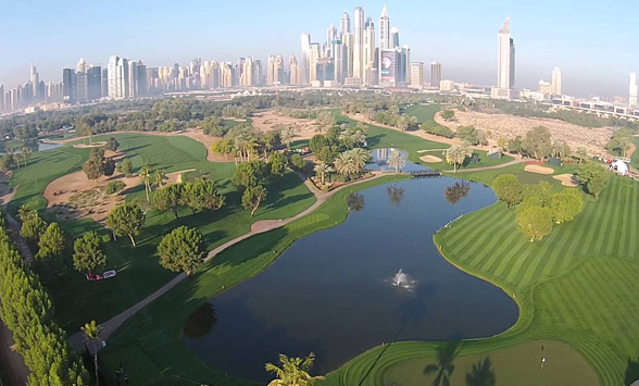 aerial view of the Emirates Golf Club with sky scrappers of Dubai City in the distance.