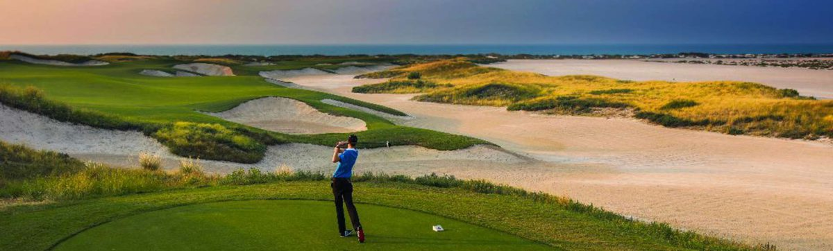 Golfer hits a tee shot past the white sand bunkers towards the ocean.