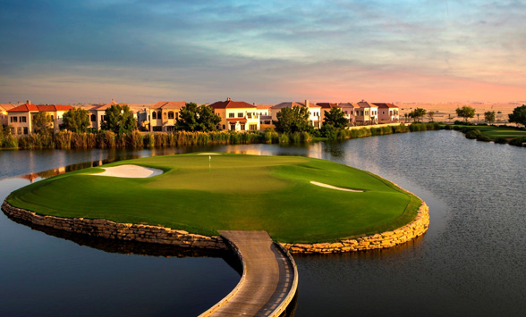 sun setting over the water surrounding the island green at Jumeirah Earth golf course.