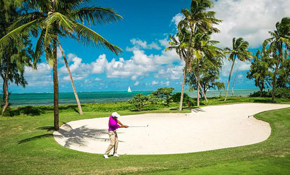 Golfer on the fairway at Anahita surrounded by palms and a turquoise blue lagoon.
