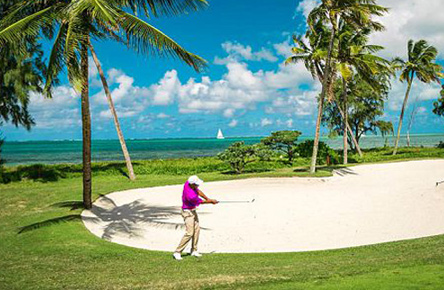 golfer playing his shot from the bunker on a palm fringed golf course in Mauritius.