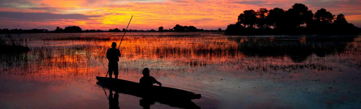 Mokoro canoe silhouetted against the Orange and red sunset in the Okovango.