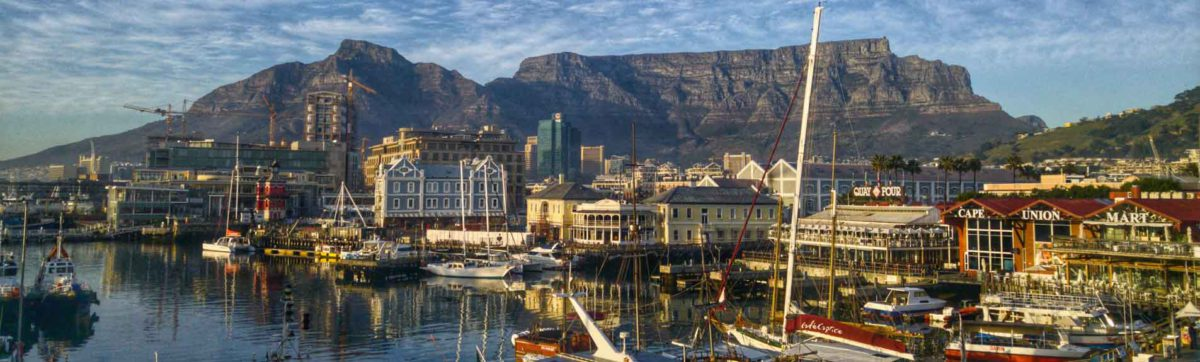 light clouds over Table Mountain and the V&A Waterfront with boats in the harbour.