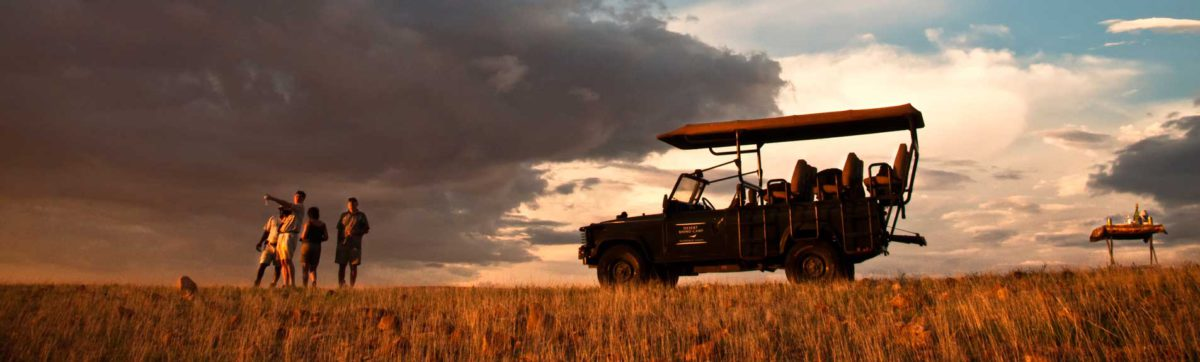 Guest enjoying sun downer drinks as part of a game drive in Namibia.