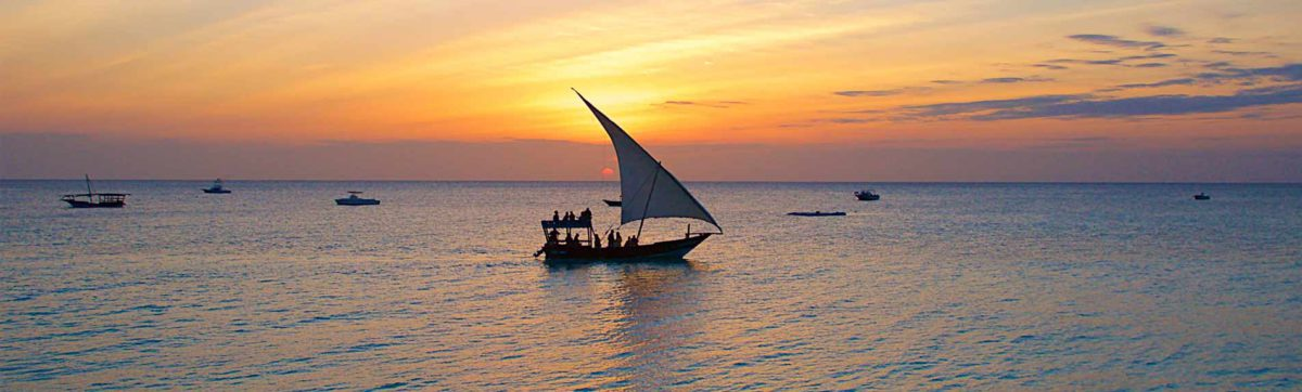dhow boat sailing on the ocean near Stone Town, Zanzibar as the sun sets.