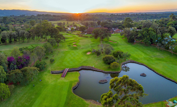 aerial view of the Karen Country Club fairways with the sun setting over Nairobi City.