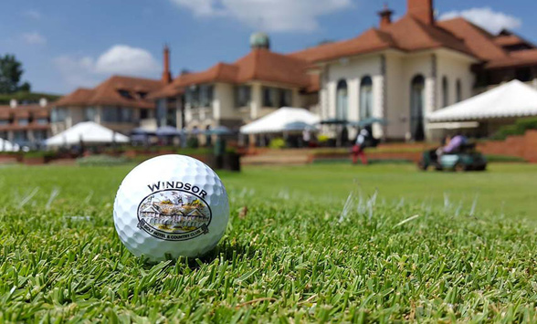 close up of golf ball with Windsor Golf Hotel logo and club house in the back ground.