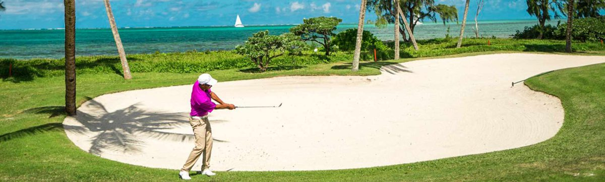 Golfer hitting his ball from the sand bunker as a yacht sails past on the azure blue sea in Mauritius