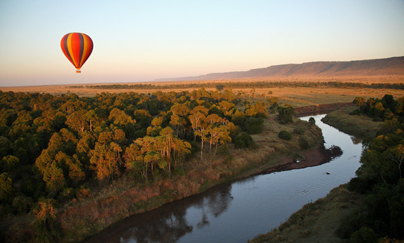 Hot air balloon travelling over a river in the masia mara
