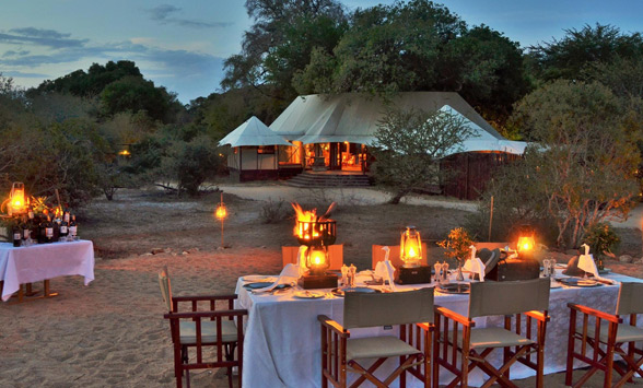 Dining tables laid up outside, around a boma fire