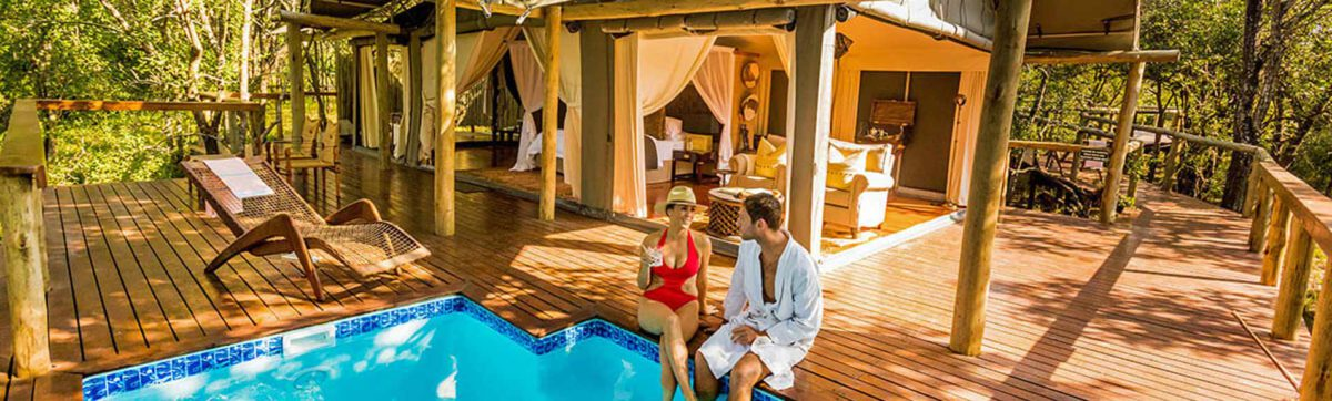 couple sitting on the deck with their feet in the plunge pool and enjoying a glass of wine.