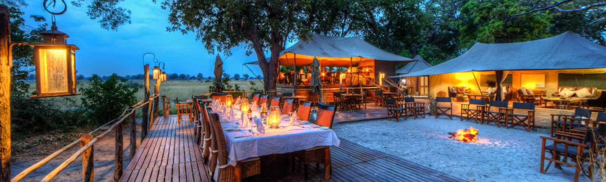 Sunset at Kadikora Safari Lodge where the dinner table is lit by hurricane lamps.