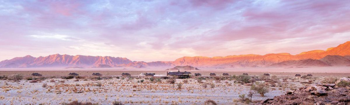 panoramic view of Hoodia Desert Lodge with mountains behind.